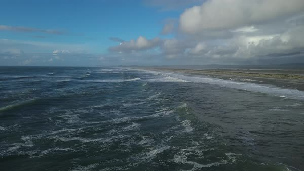 Aerial shot of waves rolling onto a beach in New Zealand Royalty-free stock video