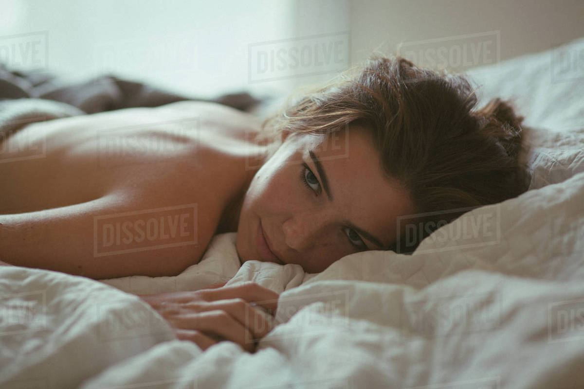 Portrait of a beautiful young woman lying on bed at home Royalty-free stock photo