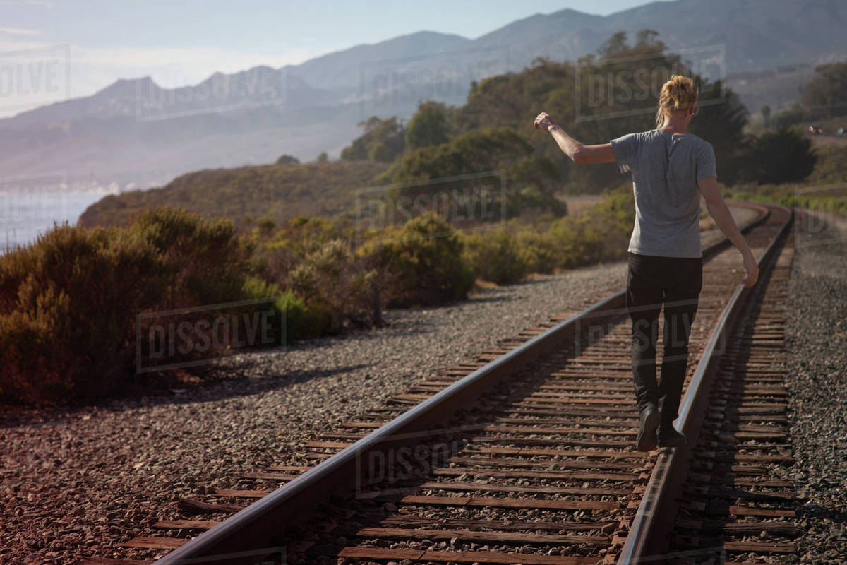 Rear view of a man walking on railroad track Royalty-free stock photo