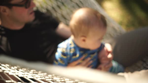 Hand-held shot of a man lying in a hammock with a baby Royalty-free stock video