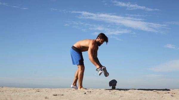 Handheld shot of a man taking off his shoes on a sandy beach Royalty-free stock video