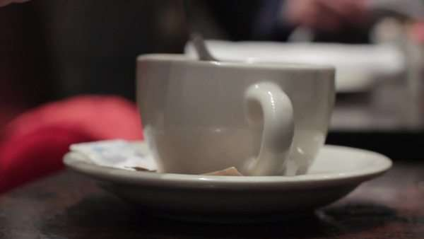 Locked off shot of a woman's hand stirring her drink with a teaspoon Royalty-free stock video