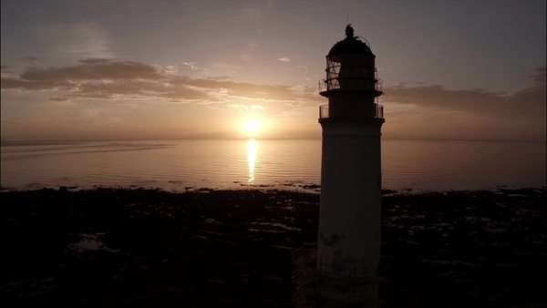Aerial shot of a lighthouse during a beautiful sunrise in Scotland with coastline in background Royalty-free stock video
