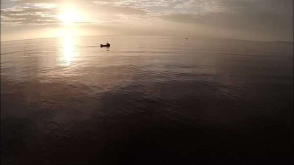 Aerial shot of a calm coastline during sunrise with small fishing vessel Royalty-free stock video