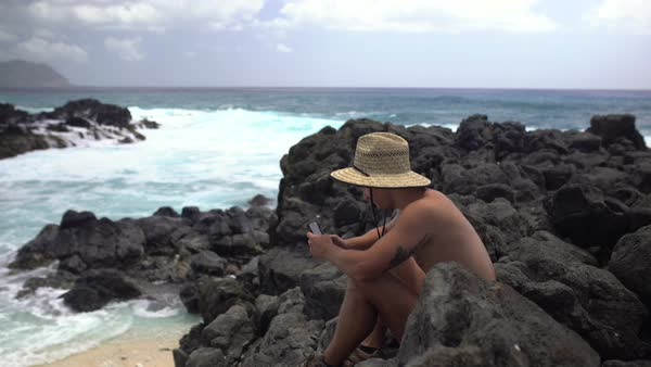 Hand-held shot of a man sitting on rocks on a beach Royalty-free stock video