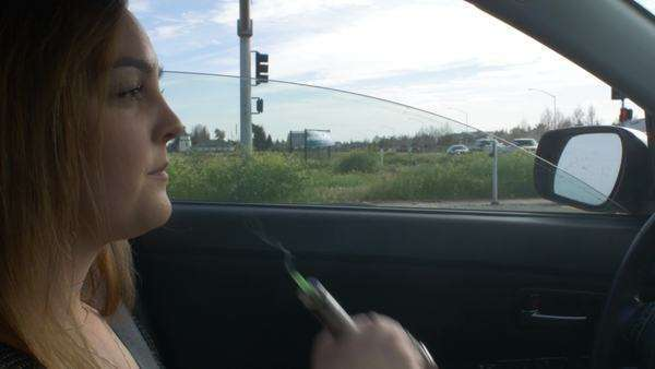 Handheld medium close up of a young woman smoking in a car Royalty-free stock video