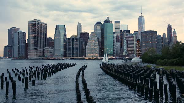 Lower Manhattan Financial District skyline skyscrapers seen from Brooklyn Bridge Park with wooden piles of Pier One in the East River Royalty-free stock video