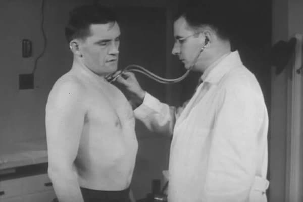 Workers receive medical checkups and doctors and nurses in industrial dispensaries diagnose and treat ailments, in 1943. Royalty-free stock video