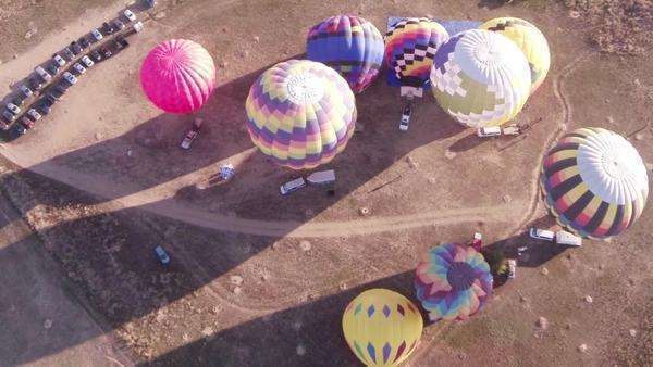 High-angle aerial shot looking down on hot air balloons being inflated. Royalty-free stock video