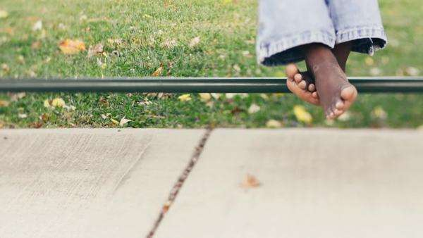 Selective Focus of an African American Child Bare Feet Sitting on A Bench in a Park Royalty-free stock video