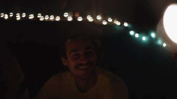 Man laughing at night with string lights overhead Royalty-free stock video