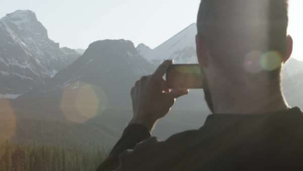 Man holds phone up in front of mountains with lens flare Royalty-free stock video