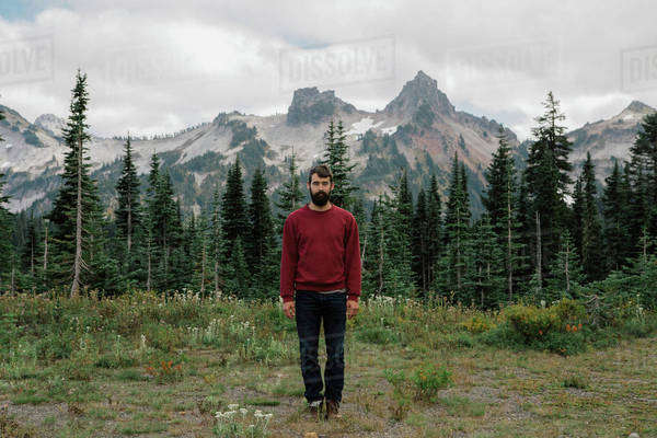 Man in red sweatshirt stands in front of mountains Royalty-free stock photo