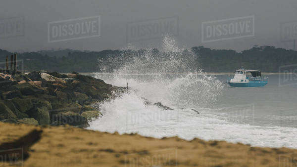 Large wave crashes on rocks with boat in background Royalty-free stock photo
