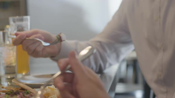 A couple's hands with food on forks ready to eat Royalty-free stock video