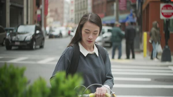 Young woman walks bike around corner of building downtown  Royalty-free stock video