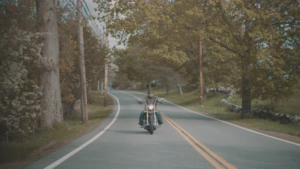 Man drives motorcycle down rural road Royalty-free stock video