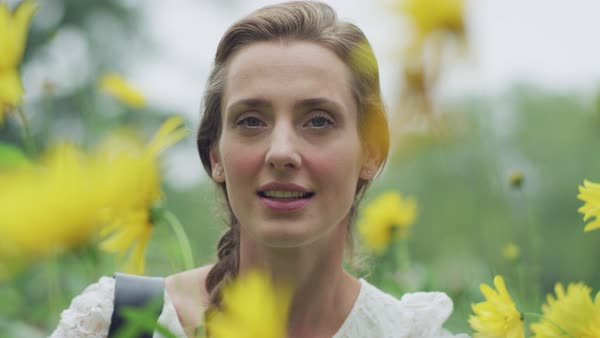 Portrait of a beautiful young woman in flower field Royalty-free stock video