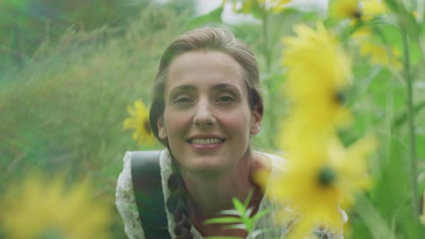 Portrait of a young woman smiling in flower field Royalty-free stock video