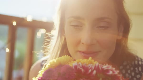 A young woman smelling flowers and smiling Royalty-free stock video