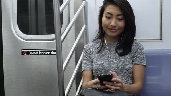 Hand-held shot of a woman using a smartphone in a subway train Royalty-free stock video