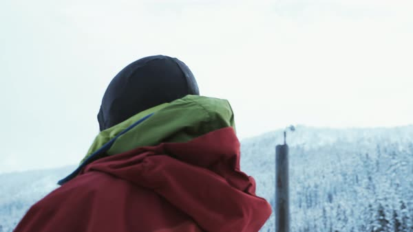 Panning shot of a man watching snow covered landscape Royalty-free stock video