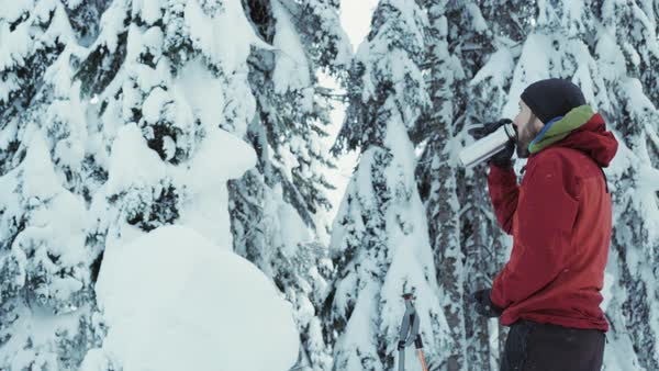 Tilt-down shot of a man drinking from insulated flask in a snow covered forest Royalty-free stock video