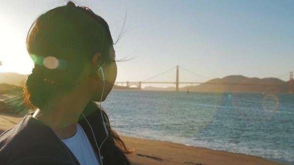 Girl listening to headphones while looking at Golden Gate Bridge in San Francisco, California.  Great view of the bridge on clear day. Royalty-free stock video