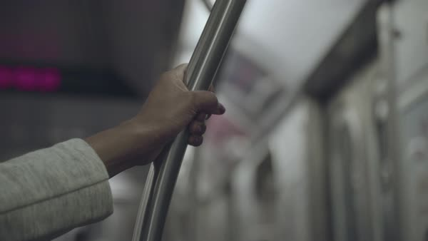 Hand-held shot of hand of a woman holding a bar in a subway train Royalty-free stock video