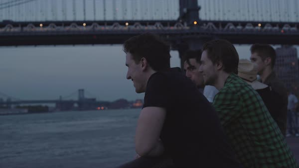 Hand-held shot of young men looking at New York from across the river Royalty-free stock video