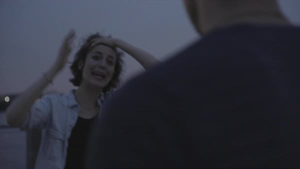 Hand-held shot of a woman shouting at a man outdoors at night Royalty-free stock video