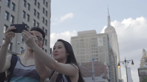 Gimbal shot of a young couple taking a photo on a street in New York City Royalty-free stock video