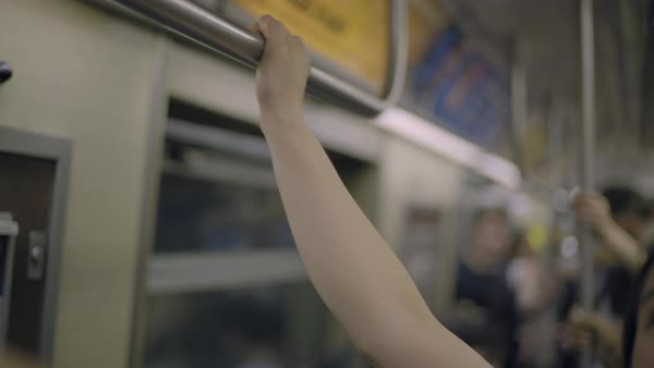 Hand-held shot of a young couple holding a bar in a subway train Royalty-free stock video