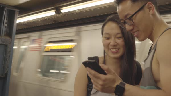 Gimbal shot of a young couple using a cell phone on a subway platform Royalty-free stock video