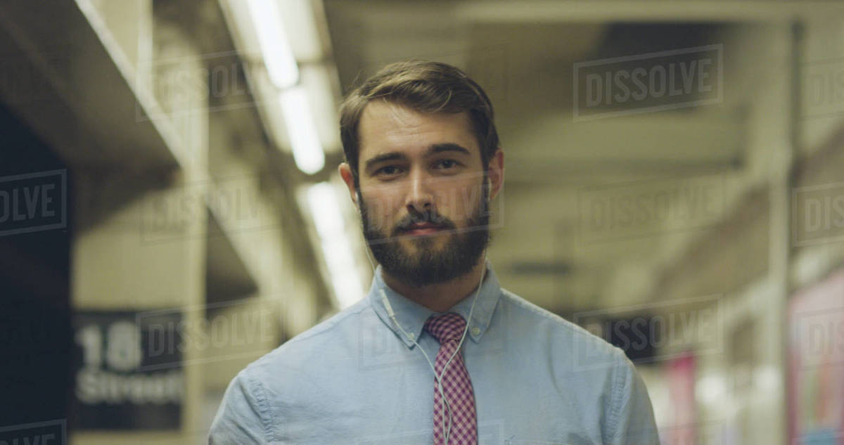 Portrait of a businessman wearing earphones listening to music while standing at subway station Royalty-free stock photo