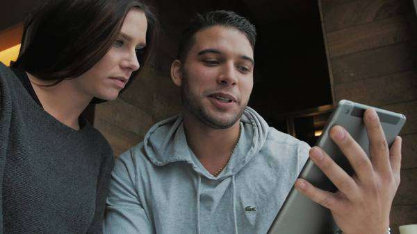 Attractive smiling couple looking at tablet in coffee shop Royalty-free stock video