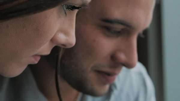 Closeup of attractive couple sitting next to window looking at tablet Royalty-free stock video