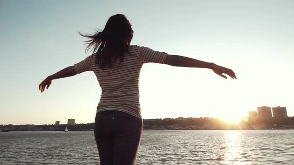 Slow motion shot of a woman raising her arms by the river Royalty-free stock video