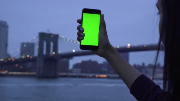 Panning shot of a woman holding a smartphone with green screen taking photographs of New York Royalty-free stock video