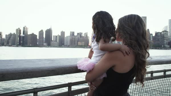 Hand-held shot of a mother holding her daughter along a riverbank Royalty-free stock video