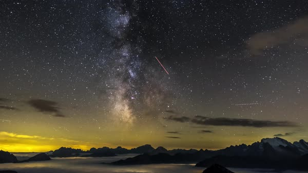 Timelapse of shooting stars and clouds moving over Marmolada mountain with Milky Way galaxy in background Royalty-free stock video