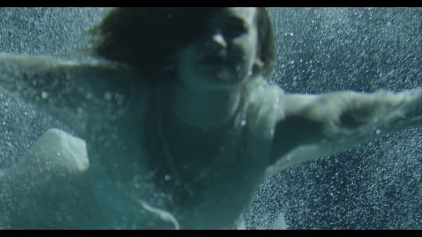 Slow motion shot of woman in white dress swimming underwater Royalty-free stock video