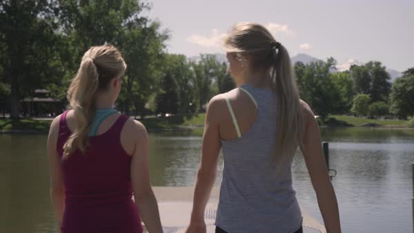 Steadicam Follow Shot Of Young Women In Activewear Walking To End Of Dock, They Reach The End And Hug And Raise Their Arms In Victory  Royalty-free stock video