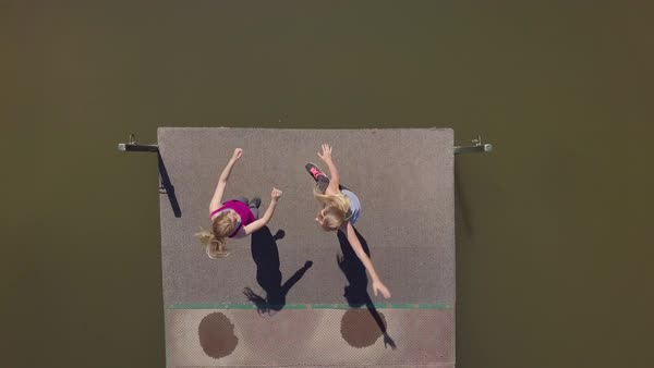 Drone Shot Of Young Women Twirling In Circles With Their Arms Raised, At The End Of A Dock, Then They Hold Hands And Exit Frame Royalty-free stock video