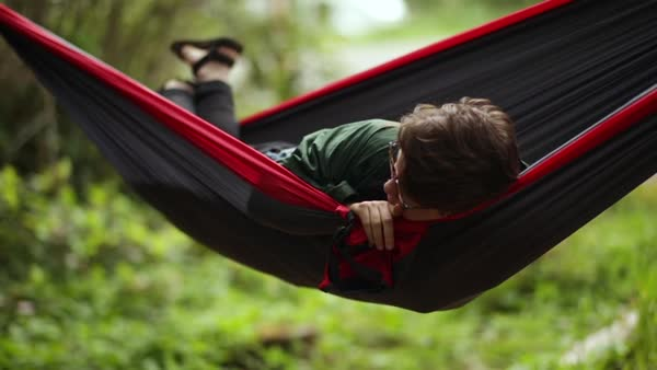 Portrait Of Happy Camper Relaxing In Hammock, They Adjust Their Glasses And Smile At Camera, Slow Motion Royalty-free stock video