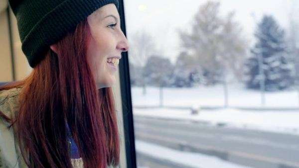 Teen girl rides train, she looks out window and smiles at the snowy landscape Royalty-free stock video