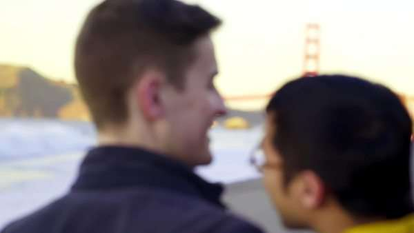 Gay couple watch the sunset on the beach (Golden Gate Bridge in background) Royalty-free stock video
