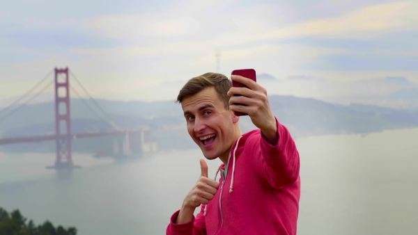 Funny man poses, gives a thumbs up, for a selfie with the Golden Gate Bridge in the background Royalty-free stock video
