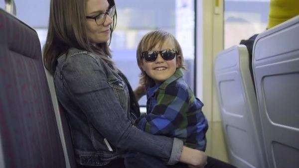 Happy little boy sits in his mother's lap, he smiles and talks on train ride Royalty-free stock video