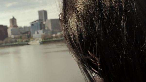 Close-up of teen looking across river at beautiful city skyline. slow motion Royalty-free stock video